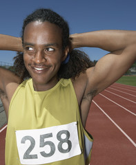 Male track athlete stretching before race