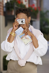 Mature woman with camera in front of face