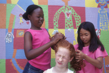 Two girls fixing friends hair