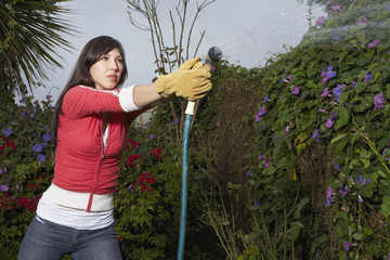Woman spraying water from hose