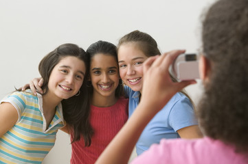Girl taking picture of three girls