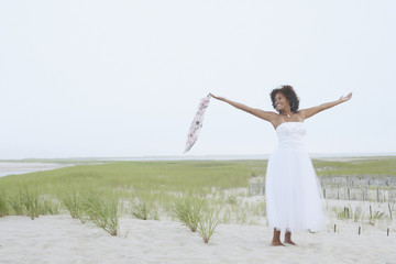 Young woman standing on the beach with her arms outstretched