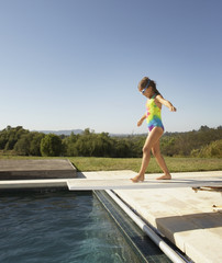Young girl walking on diving board