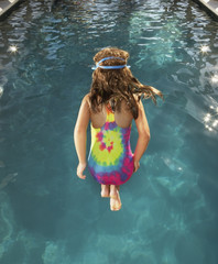 Young girl in mid-air above a swimming pool