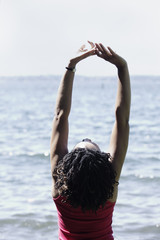 Woman stretching at ocean