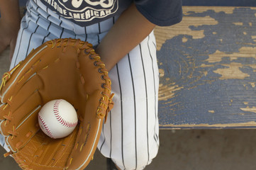 Boy holding baseball in baseball glove