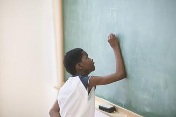 Young boy writing on chalkboard