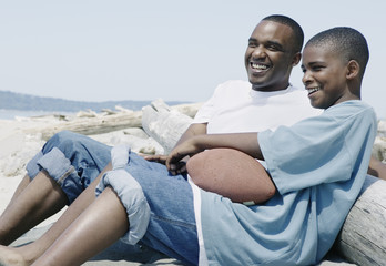 Father and son relaxing at beach with football