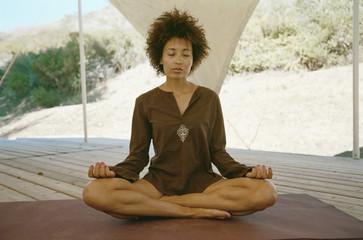 African American woman meditating in screened area