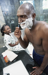 Girl watching man shave