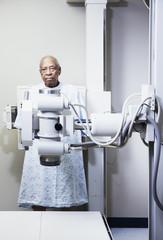 Portrait of elderly man in gown behind x-ray machine