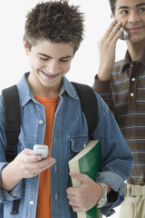 Two teenage boys standing with cell phones