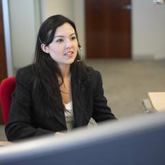 Woman sitting in office wearing earpiece
