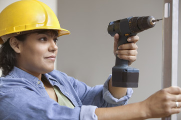 Woman construction worker with power drill and level