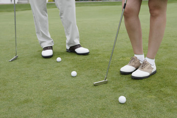 Low section of couple's feet playing golf