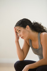 Sweating woman in gym clothes resting