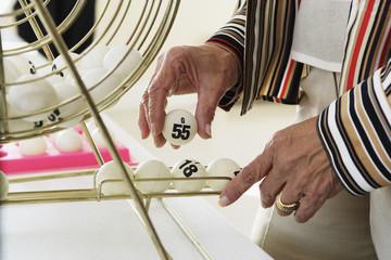 Elderly woman picking up a bingo ball