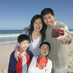 Family taking a self-portrait on the beach