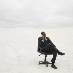 African businessman sitting and talking on cell phone in the desert