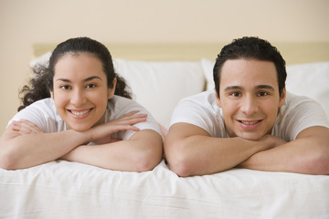 Hispanic couple lying on the bed