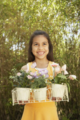 Hispanic girl holding potted flowers outdoors