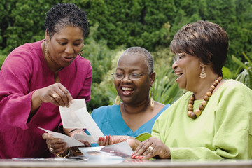Three middle-aged African women looking at photographs