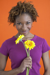 African woman smiling and holding flowers