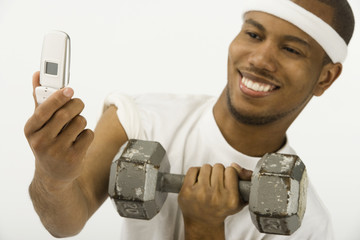 African man holding dumbbell and cell phone