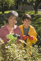 Grandmother and grandson watering plants