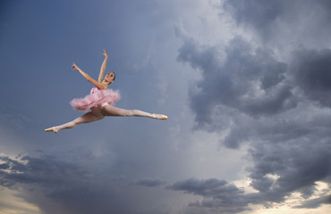 Female ballet dancer in mid air in sky
