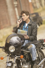 Man sitting on motorcycle using cell phone