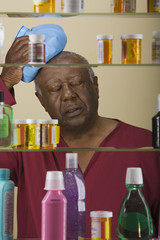 Sick senior African man in front of medicine cabinet