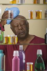 Sick senior African man in front of medicine cabinet