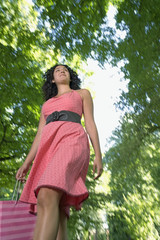 Low angle view of young woman in park with shopping bag