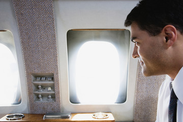 Businessman looking out window on private airplane