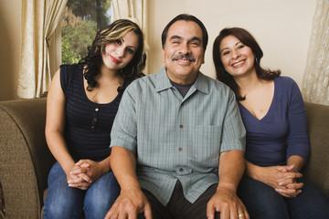 Portrait of Hispanic family on sofa