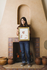 Hispanic teenaged girl holding baby photograph