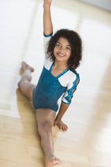 Young female gymnast doing split
