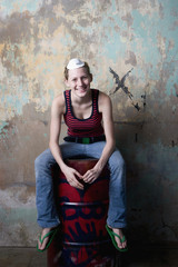 Mixed Race girl sitting on metal barrel