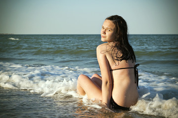 girl in a bathing suit sitting in shallow water;