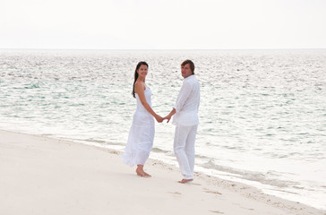 Picture of romantic young couple having a walking on the sea sho