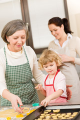 Little girl with grandmother cutting out cookies