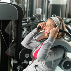 Fitness center senior woman exercise abs muscles