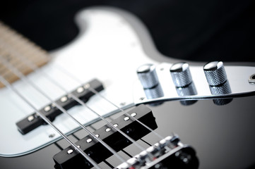 close up of a black electric bass glossy on dark background