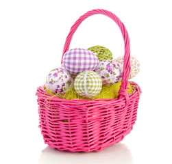 cheerful easter eggs in a pink wicker basket isolated over white