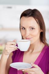 lächelnde frau genießt eine tasse kaffee