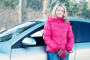 Blond woman standing by her car outdoors in winter forest