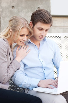 Portrait of a happy young professional couple using laptop