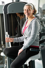 Senior woman relax sitting by fitness machine