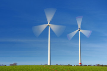 Two wind turbines in movement on a green field